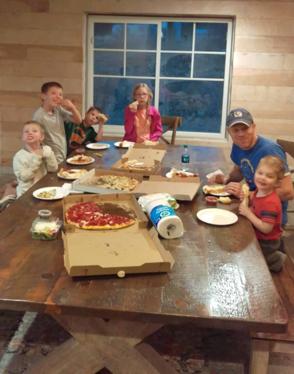 a family around their new kitchen table eating pizza