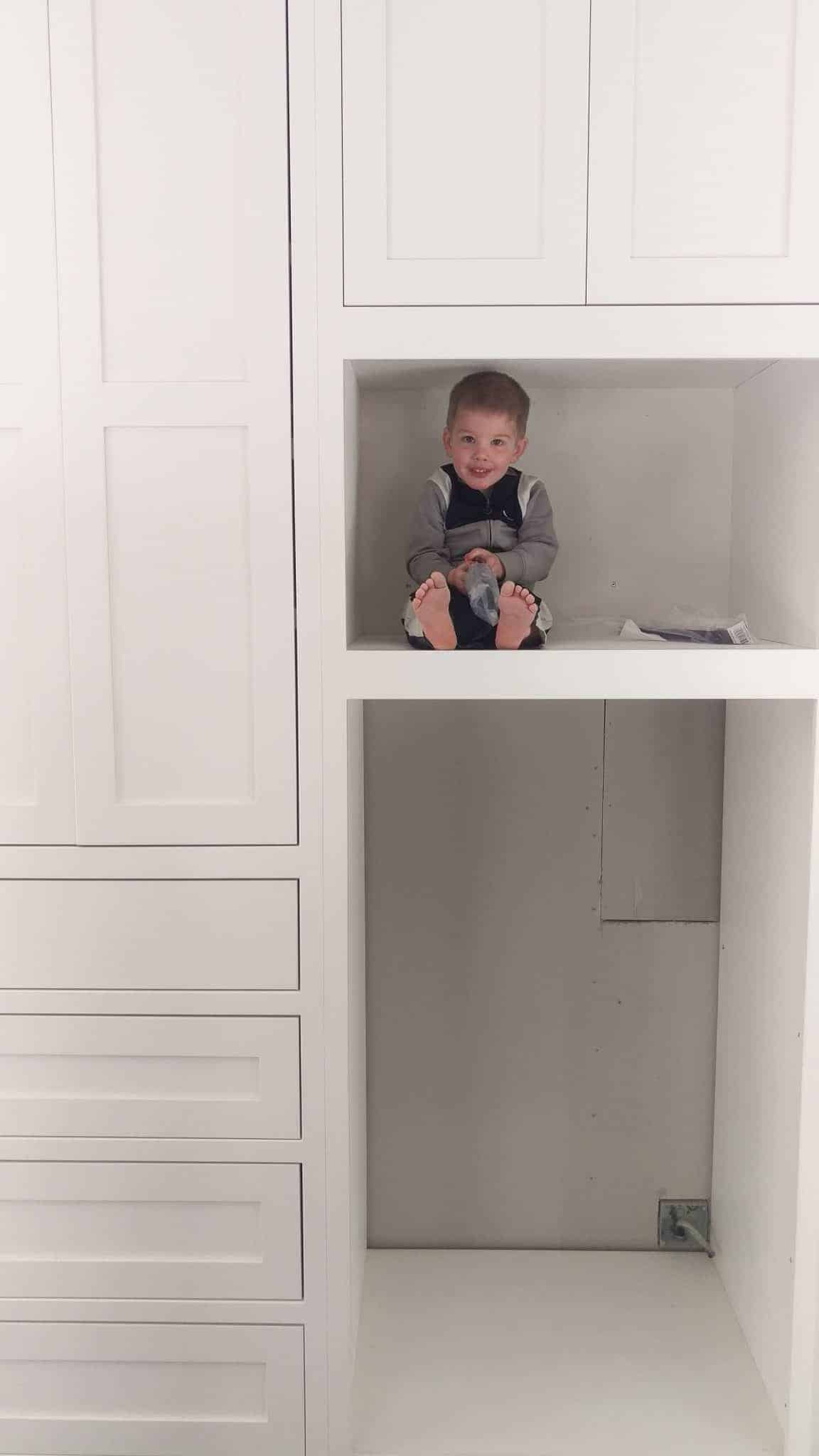 a toddler sitting inside the installed cabinets