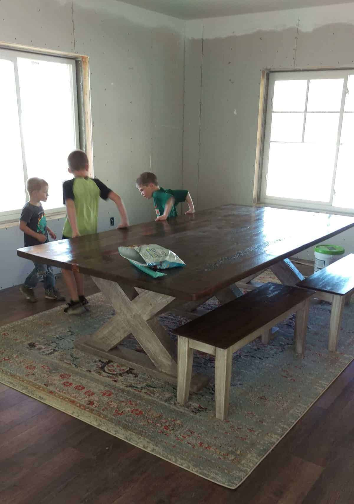 a large rug with a wooden table over it. three young boys play next to it.