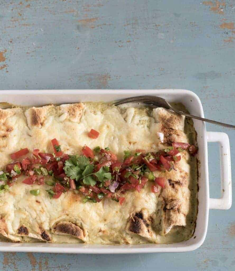 A white rectangular baking dish filled with baked enchiladas topped with melted cheese, pico de gallo and fresh cilantro