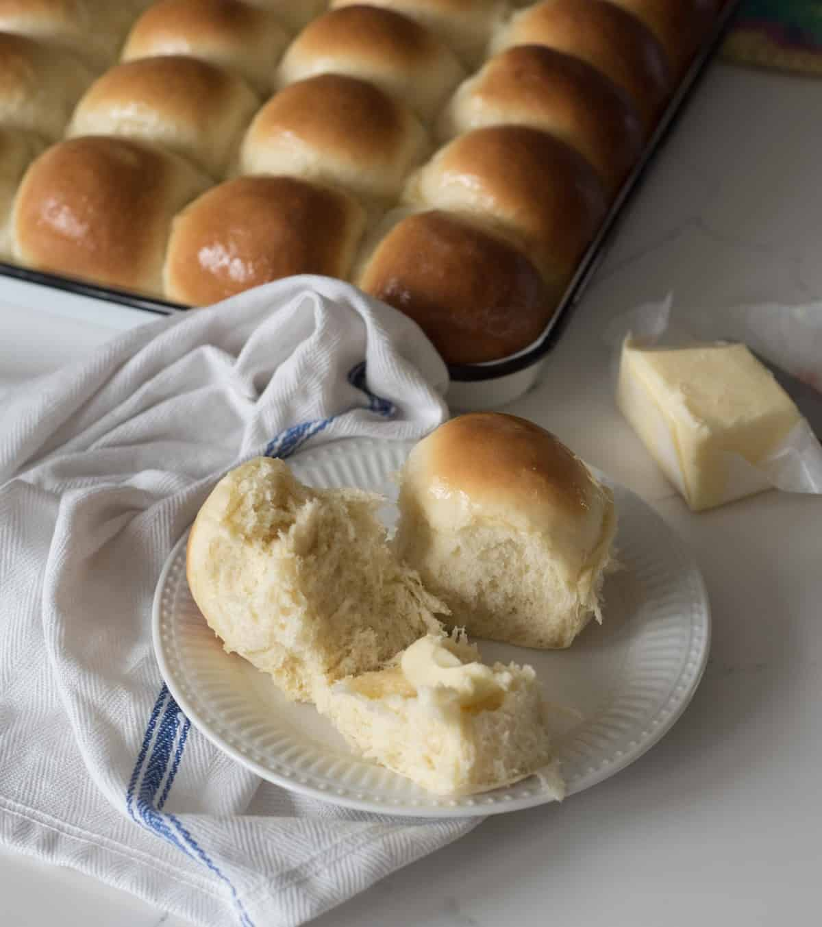 Golden dinner rolls in the pan with two removed onto a plate, broken with butter inside and waiting to be eaten.