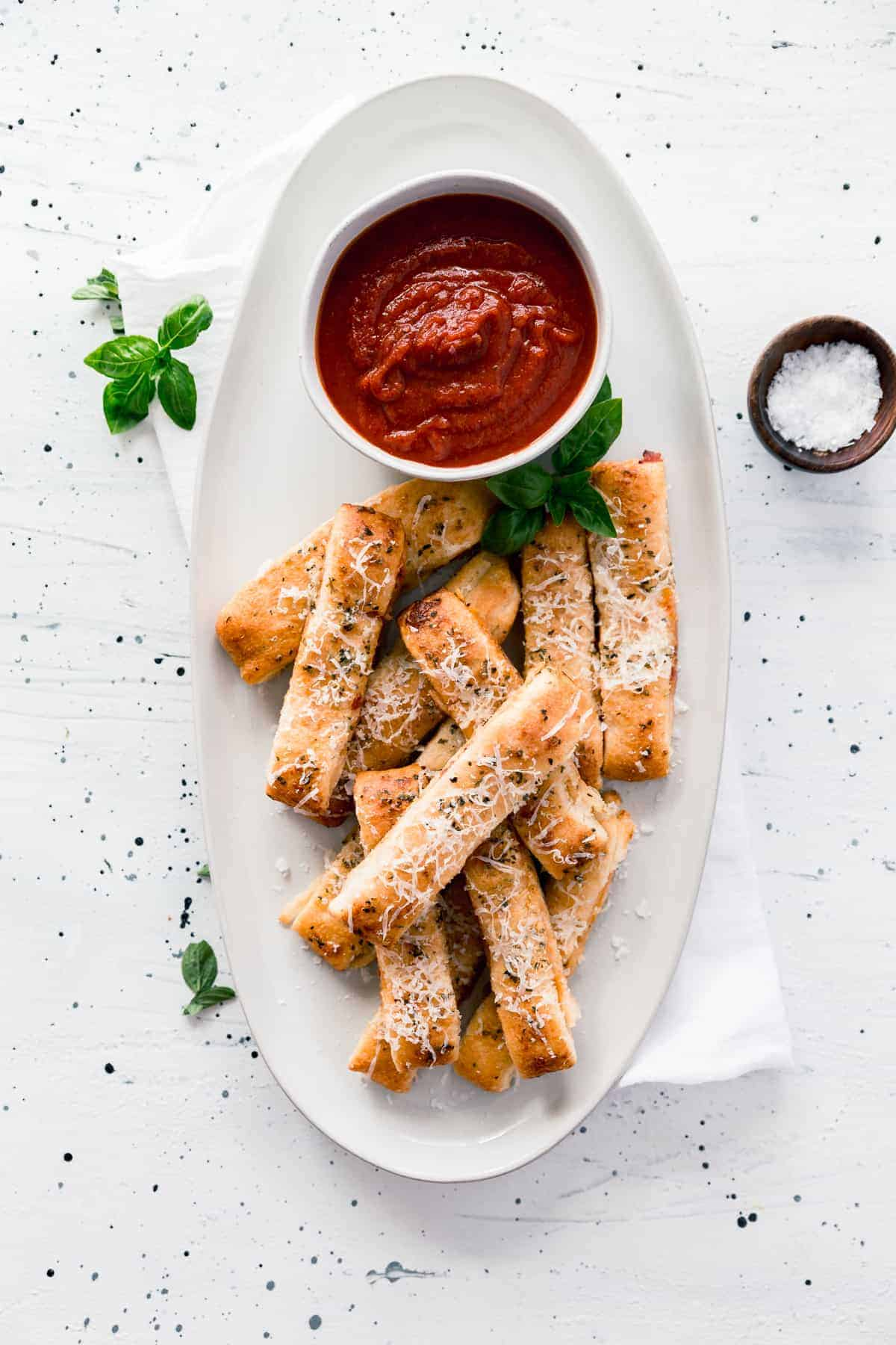 Easy cheesy pizza sticks are made with store-bought dough, pizza sauce, and cheese and only take 20 minutes to make, start to finish.