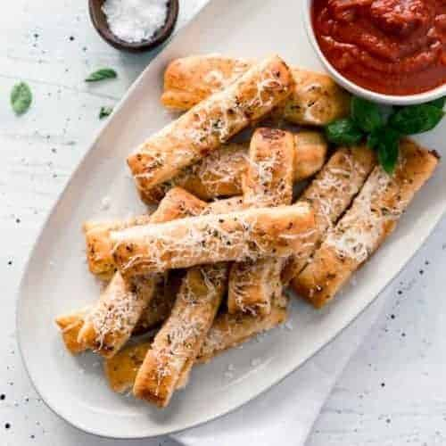 Plate of cheesy pizza sticks with cup of sauce