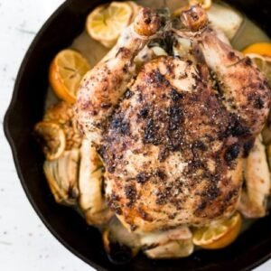 Image of a whole baked chicken in a pan with halved lemons