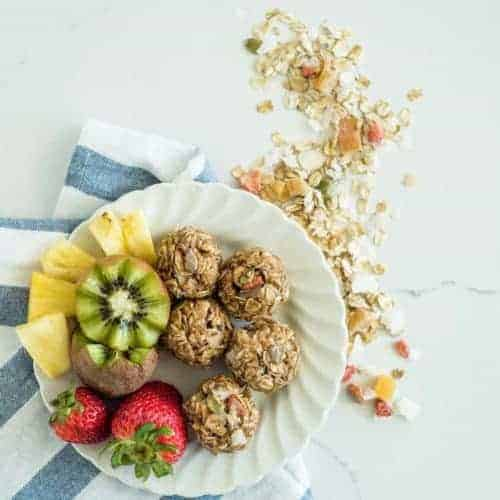 A plate with 3-ingredient muesli bites with whole strawberries, halved kiwi and pineapple chunks