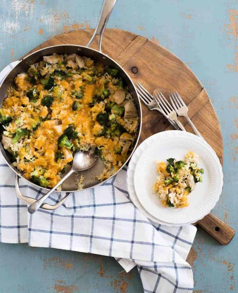 A skillet with chicken broccoli rice casserole with melted cheese and a white round plate with a serving of chicken broccoli rice casserole on a wooden board with a plaid cloth