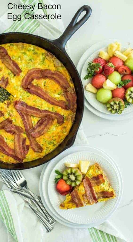 Title Image for Cheesy Bacon Egg Casserole, a round white plate with a slice of cheesy bacon egg casserole and fresh fruit, a cast-iron skillet of cheesy bacon egg casserole and a round white plate of fresh fruit