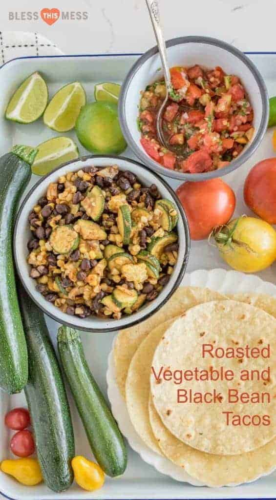Tortilla shells, whole zucchini, yellow tomatoes, lime wedges, a bowl of corn with black beans and zucchini, a bowl of fresh salsa