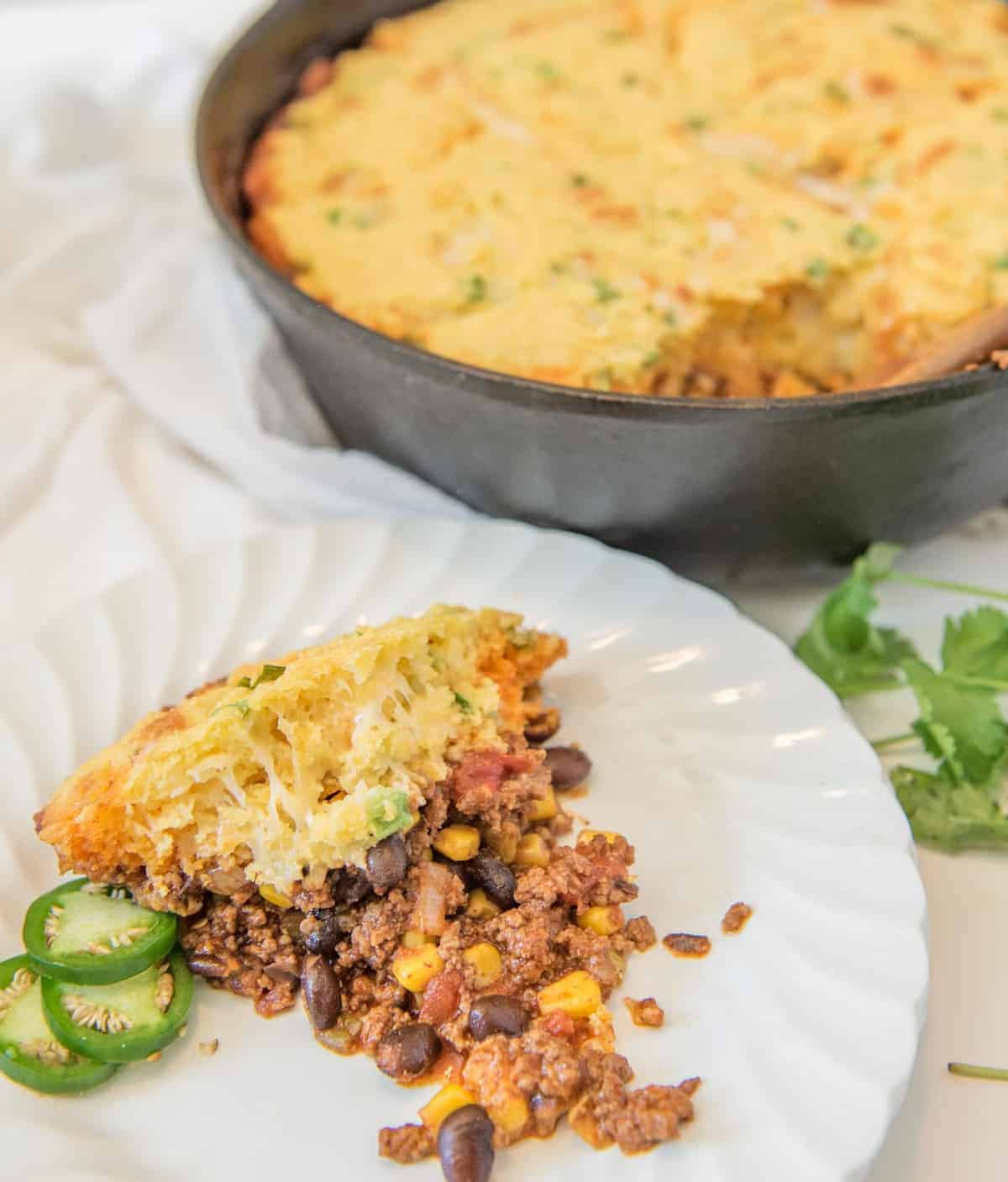 One Pan Tamale pie is made with a rich meat and vegetable filling topped with a golden cornbread crust that has cheese and green onions in it, all made in one skillet.