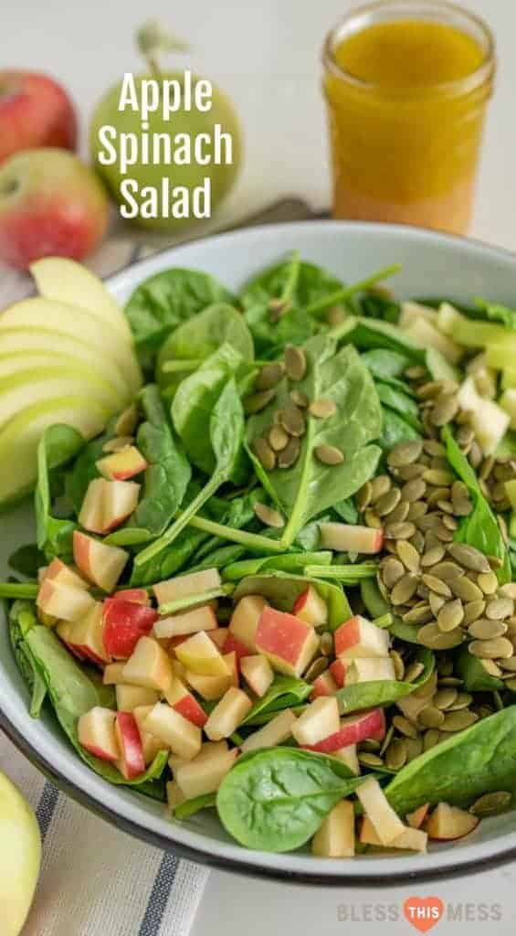 Title Image for Apple Spinach Salad and a large white bowl with baby spinach leaves, diced apple, and pumpkin seeds