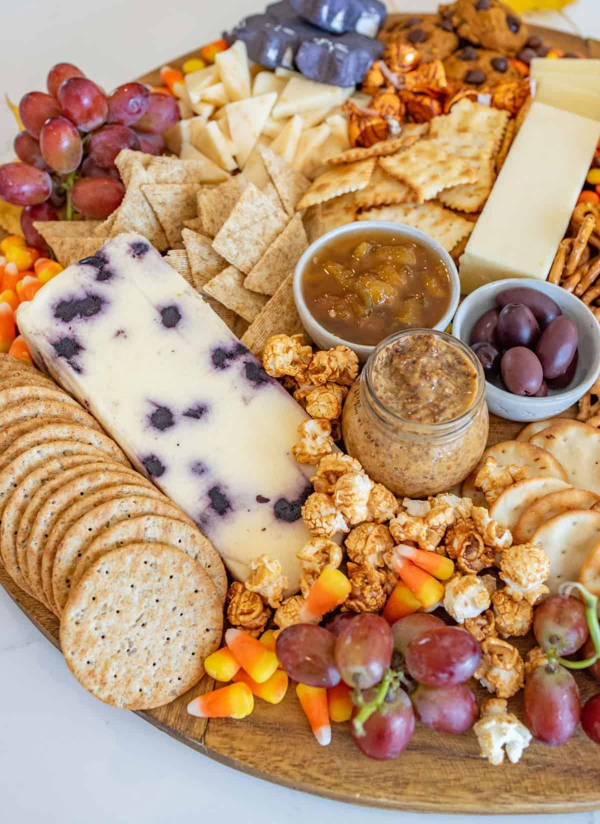 Fun and festive Halloween Cheese board made with simple cheese, crackers, pumpkins for garnish, and or coarse, lots of Halloween candy.