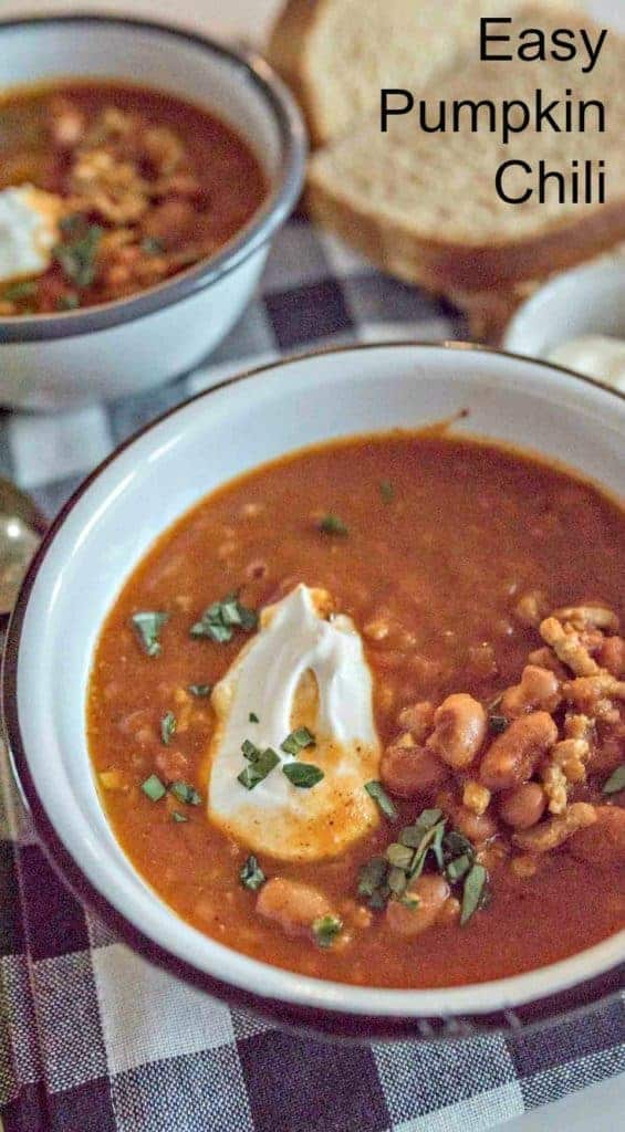 A bowl of Easy Pumpkin Chili garnished with sour cream and fresh herbs