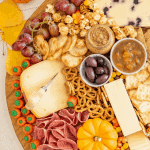 Title Image for Halloween Cheese Board with crackers, pretzels, cheeses, meats, fall-colored candies, mini gourds