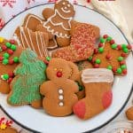 Title Image for 6 Easy Gingerbread Decorating Ideas and a white plate of gingerbread cookies in a variety of shapes and decorations