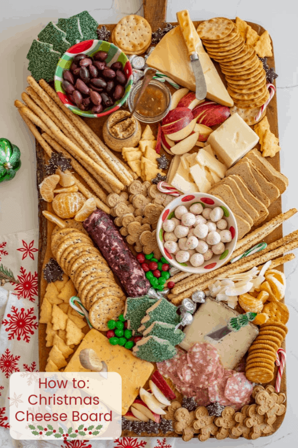 Title Image for How to: Christmas Cheese Board and a large wooden board of Christmas cookies, candy canes, crackers, meats, cheeses, olives, apples, and spreads