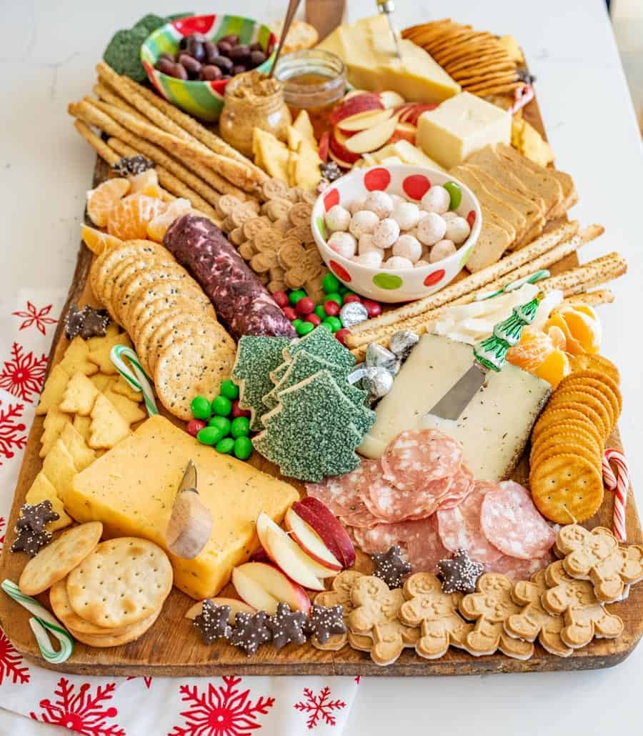 How to make a DIY Christmas Cheese board for a party complete with what cheese to buy, how to make it festive, and more!