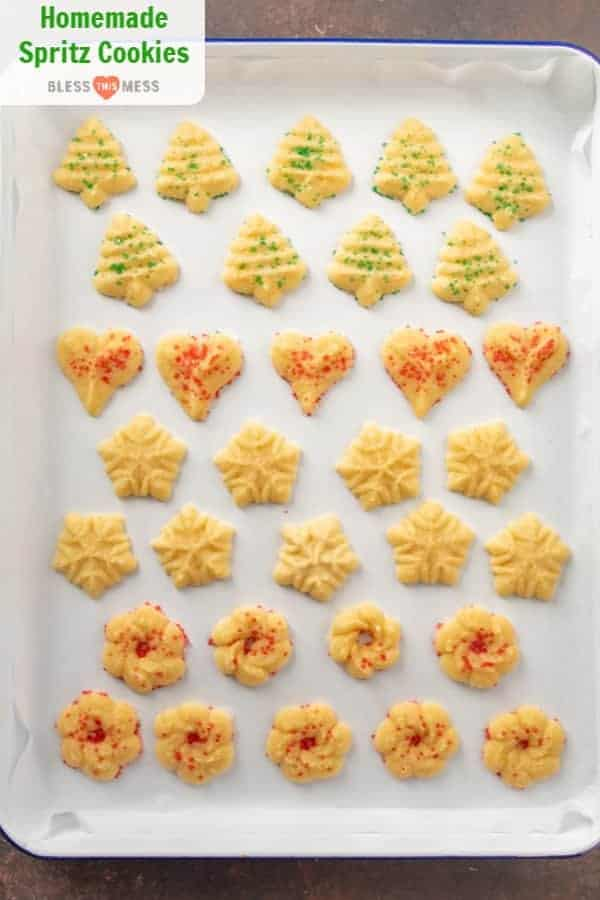 Top view of a parchment-lined baking sheet with four shapes of spritz cookies with red and green sprinkles