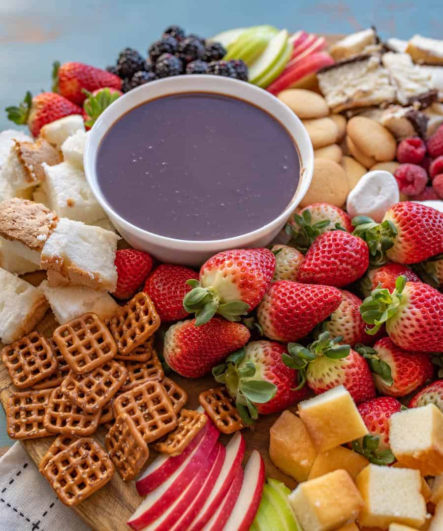 Quick and easy chocolate fondue made with 4 ingredients and you don't even need a fondue pot to make it! Perfect to dip in berries, cookies, and more.