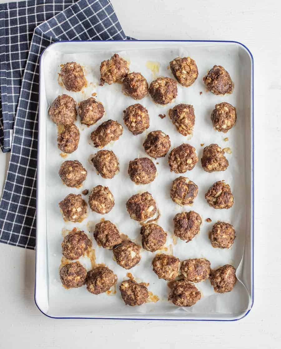 Cooked meatballs on a baking sheet after coming out of the oven.
