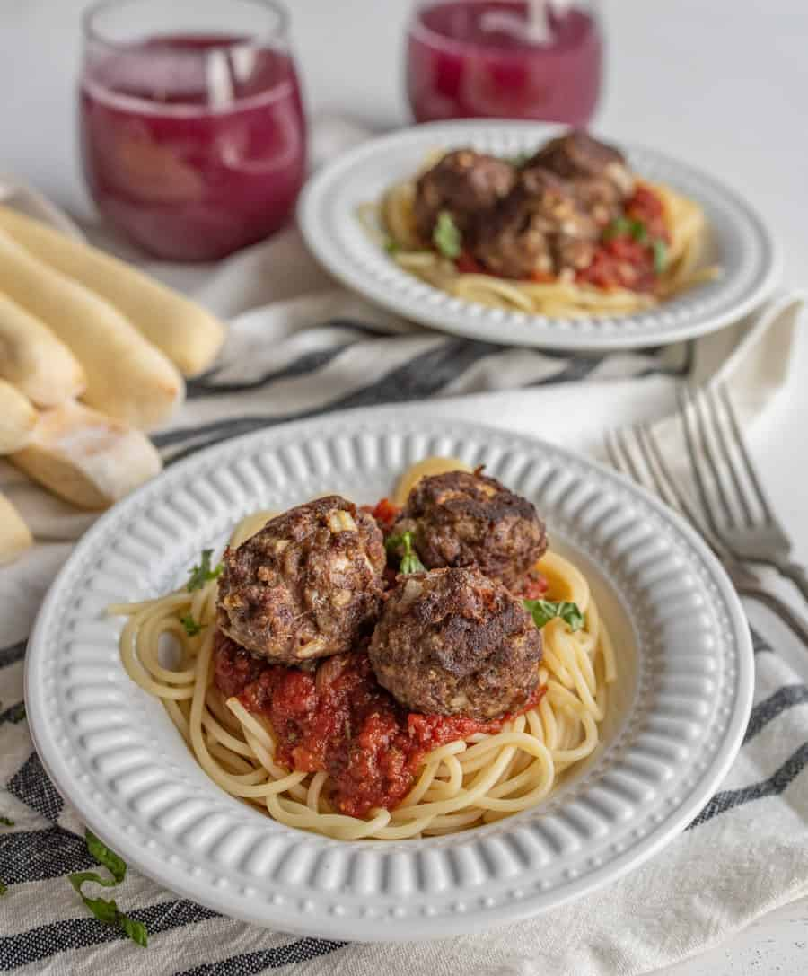 Homemade meatballs on top of a plate of spaghetti with marinara sauce with grape juice and bread sticks in the background.