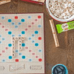A Scrabble game board spelling out Bobs Better Bars with two types of Bobs Better Bars, a beverage and a big bowl of popcorn