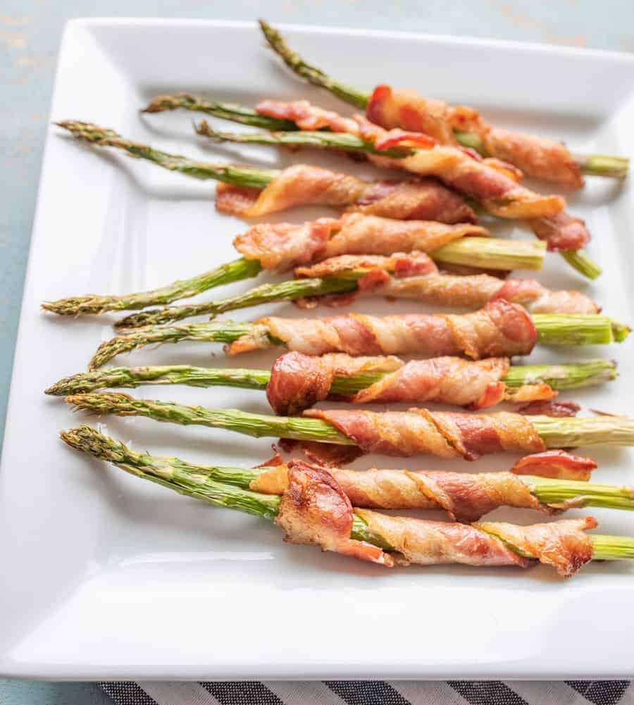 Baked bacon wrapped asparagus cooked crisp and ready to serve on a white plate.