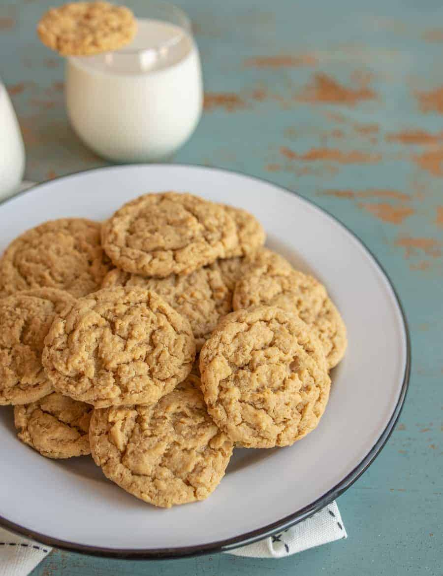Baked peanut butter oatmeal cookies stacked high on a plate with a glass of milk behind it.
