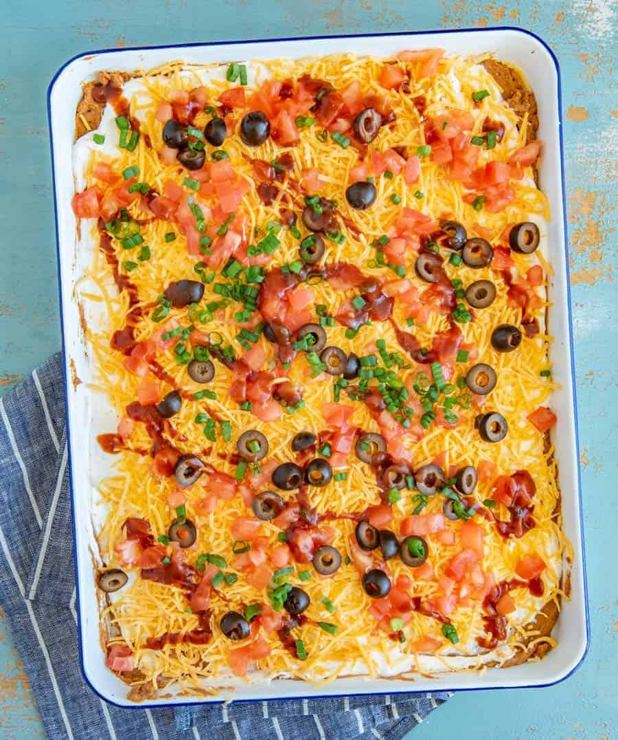 Bring the fiesta to your taste buds with this classic rendition of everyone's favorite Bean Dip. Refried beans, sour cream, cheese, tomatoes, black olives, and green onion meld with taco seasoning and salsa for a festive kick that's sure to impress.
