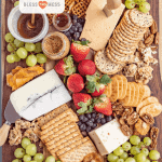 Title Image for DIY Cheese Board and a variety of cheeses, crackers, fruits, nuts and spreads on a wooden board
