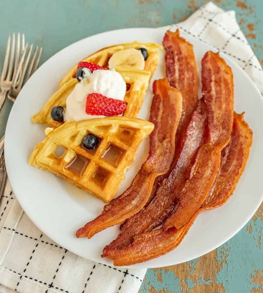 Tips and tricks you need to know so that you can cook crispy bacon in a cast iron skillet any day of the week. Bacon and waffles on a plate.