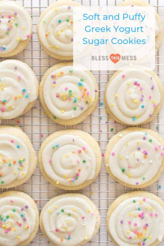 Title Image for Soft and Puffy Greek Yogurt Sugar Cookies and a dozen frosted sugar cookies with colorful sprinkles on a cooling rack