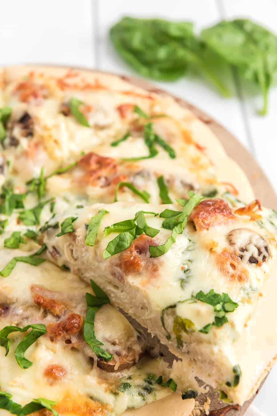Take your homemade pizza to new heights with this recipe featuring chicken, bacon, and mushrooms slathered in melted cheese and creamy sauce.