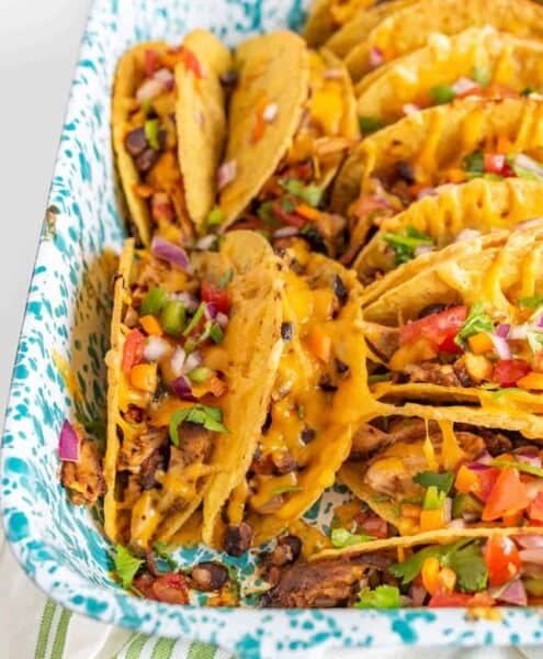 Crispy and Crunchy Baked Chicken Tacos are a quickly thrown-together and satisfying meal, complete with baked chicken, taco seasoning, black beans, hard taco shells, and plenty of shredded cheddar cheese.