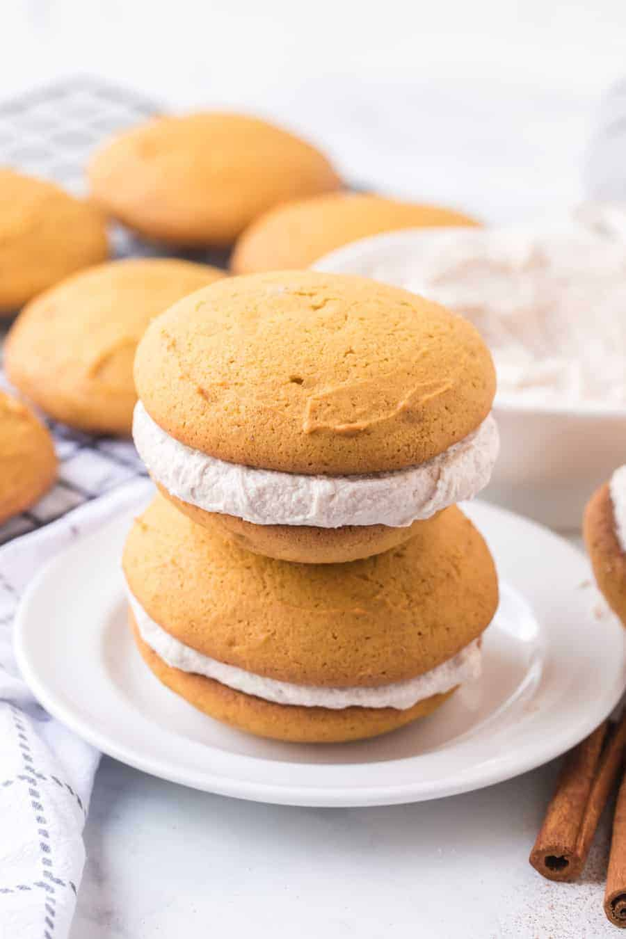 Brace yourselves for bites of heaven -- these pumpkin whoopie pies with whipped cinnamon filling are the perfectly sweet and soft, cream-filled cookie sandwiches you need this fall... and probably year-round, too. #whoopiepie #whoopiepierecipe #pumpkinwhoopiepie #pumpkin #pumkpindessert #pumpkinrecipe
