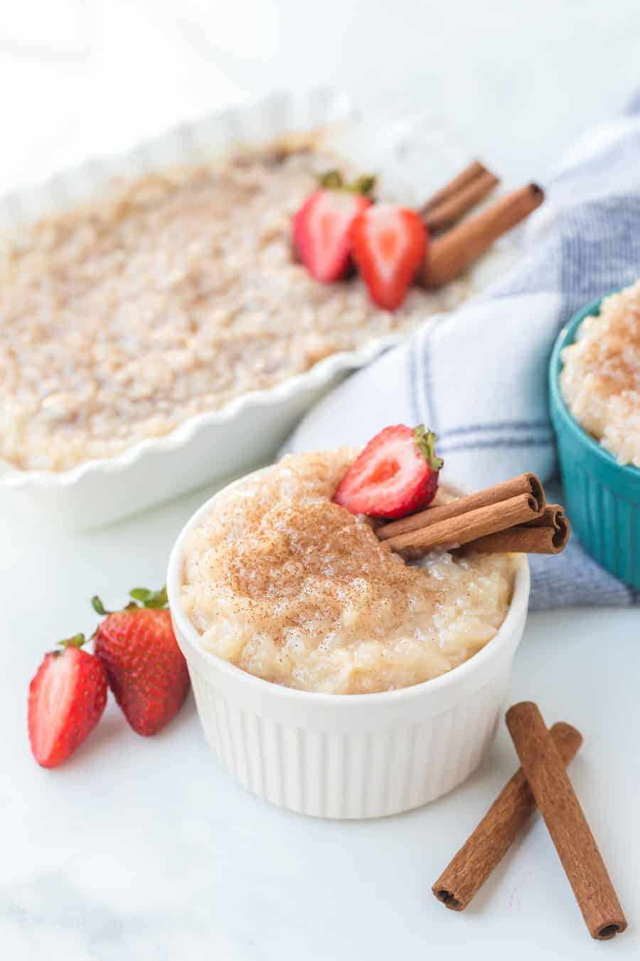 Rice pudding with strawberries and cinnamon sticks in ramekins