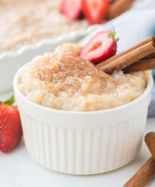 Rice pudding in white ramekin with strawberries and cinnamon sticks
