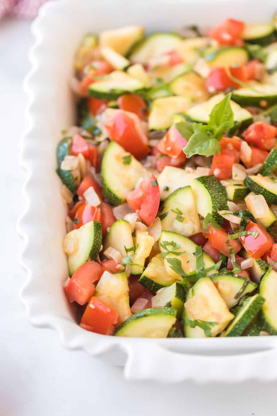 This zucchini side dish is full of onion, tomato, herbs, and of course zucchini to make a bright and fresh side that tastes out-of-this-world delicious! #zucchini #zucchiniside #easyzucchinirecipe #zucchinimedley