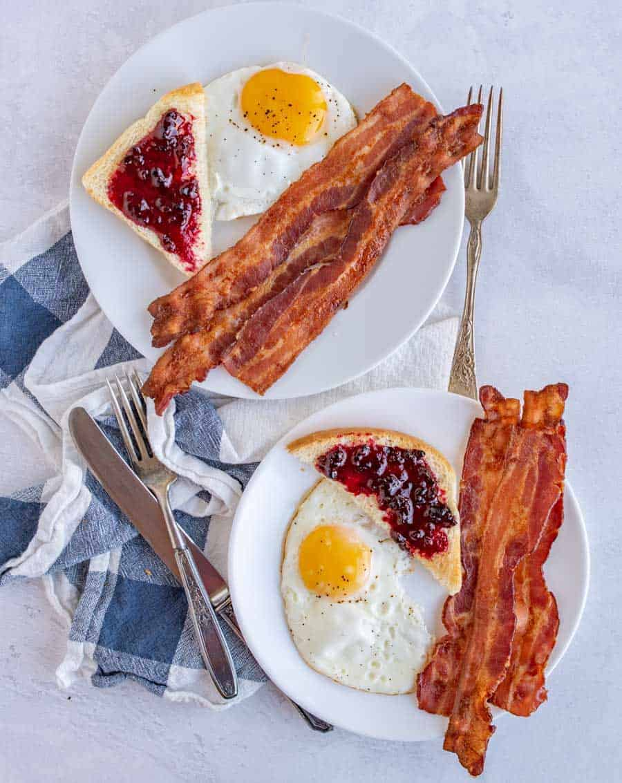 Baking bacon in the oven is the simplest way to make a large or small amount of crispy bacon -- with minimal cleanup! This easy bacon recipe comes out perfect every time. Anyone can make perfect bacon every time with this easy-to-follow oven recipe! #bacon #ovenbacon #bakedbacon #easybacon #baconrecipe #howtomakebacon