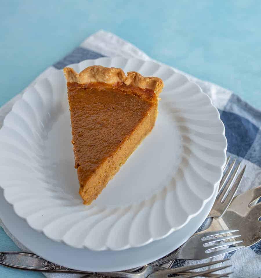 A piece of pumpkin pie on a white dessert plate.