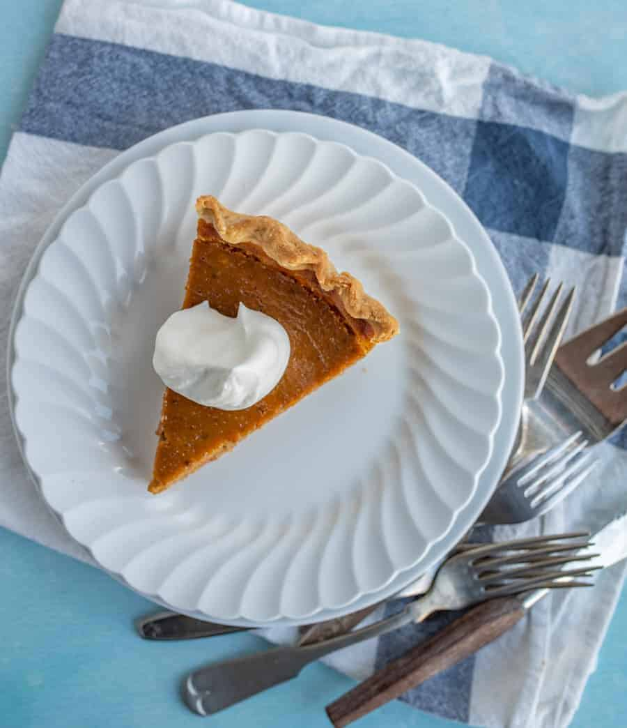 An overhead shot of a piece of pumpkin pie with a dollop of whipping cream on top.