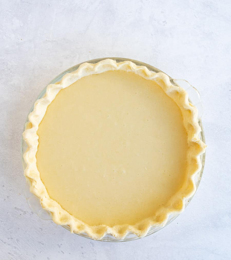 A perfect pie with pinched crust and a yellow inside is in a clear pie dish on a white marbled counter.