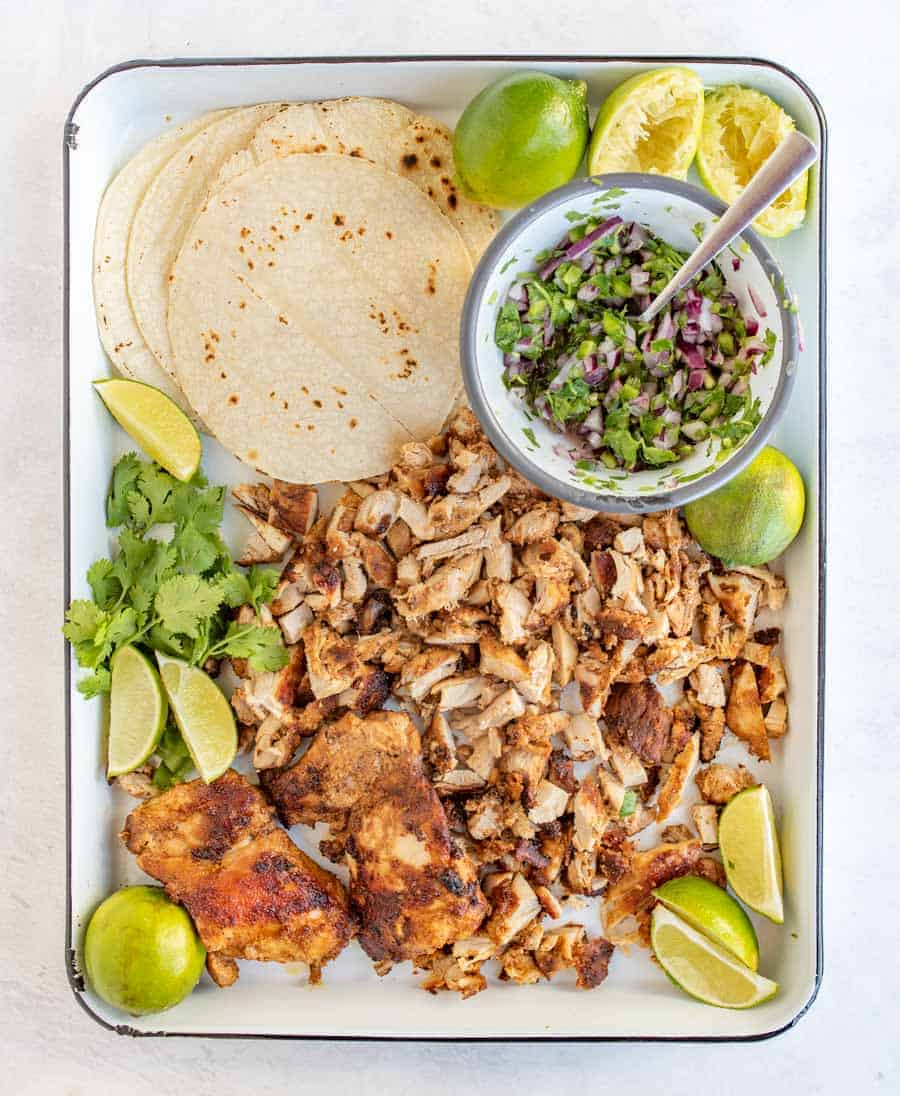 lime wedges, cilantro, red onion, chicken and tortillas on white tray