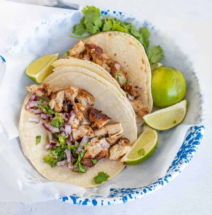chicken tacos in two tortillas in bowl with cilantro and lime wedges
