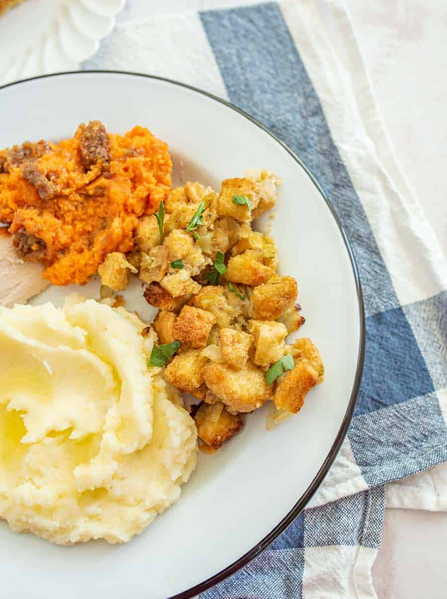 Most of a white dinner plate with a dark green outline is shown. The dinner plate has mashed potatoes with butter melting on them, a small piece of turkey can be seen, a serving of sweet potato casserole, and stuffing are also on the plate. Underneath the plate is a white dishtowel with a blue stripe and in the upper left hand corner, you can see a slice of pumpkin pie on a fancy white salad plate.
