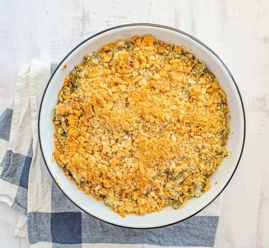 Green bean casserole in white baking dish on blue and white towel