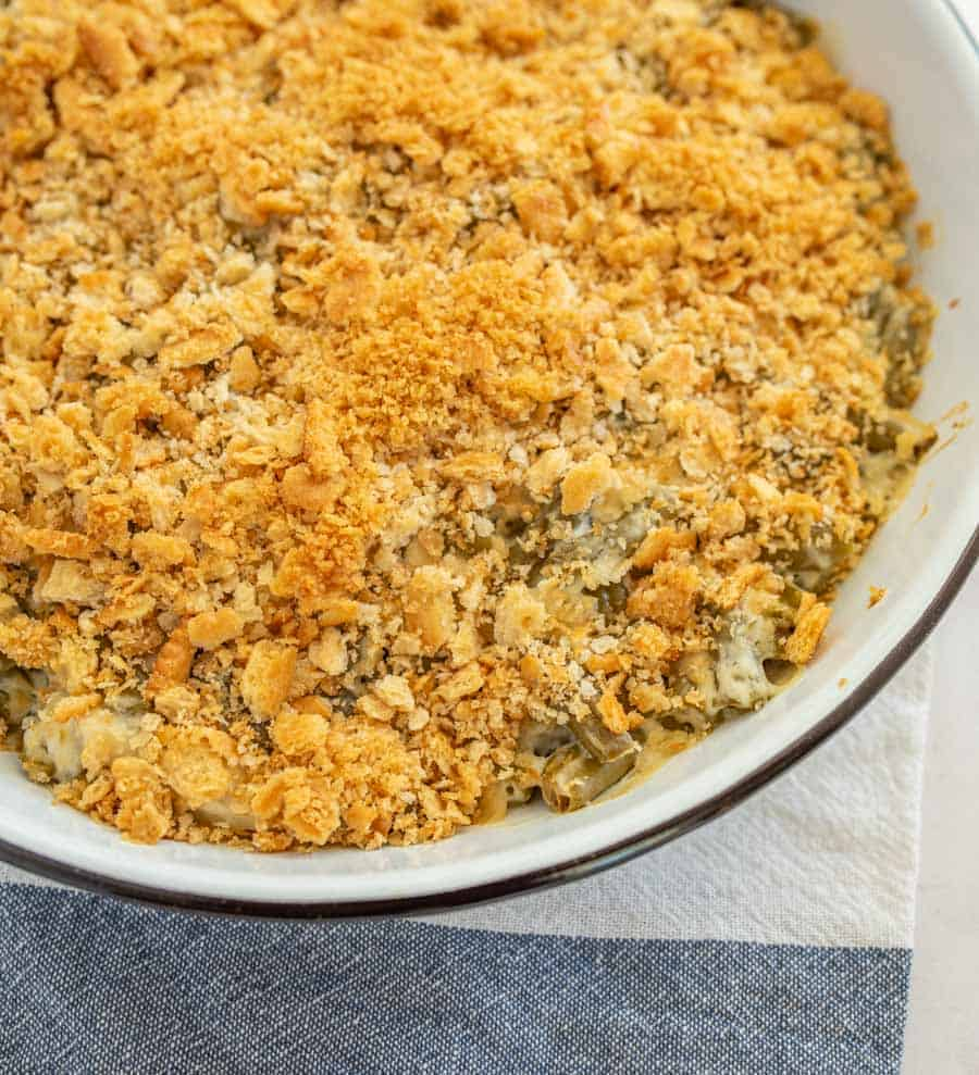 closeup of green bean casserole in round white casserole dish on blue and white towel