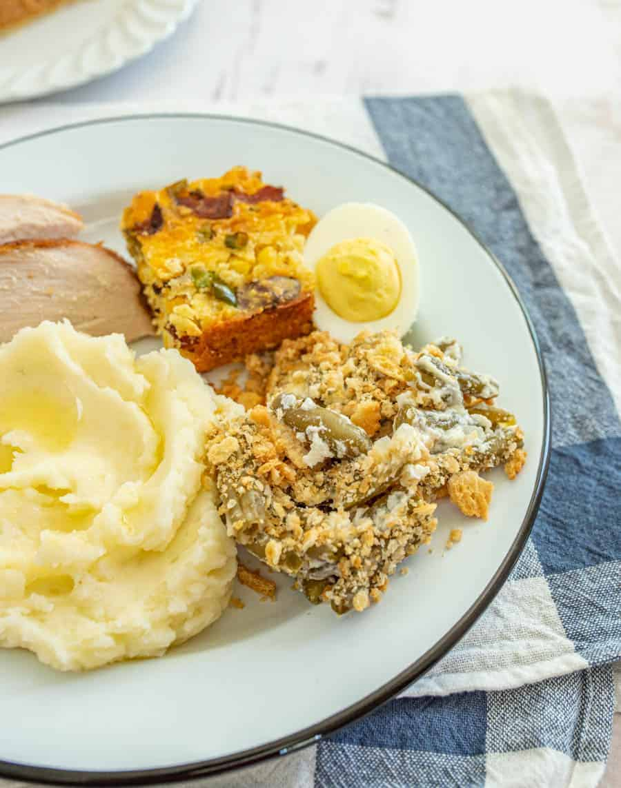 Green bean casserole with mashed potatoes turkey and deviled eggs on round white plate