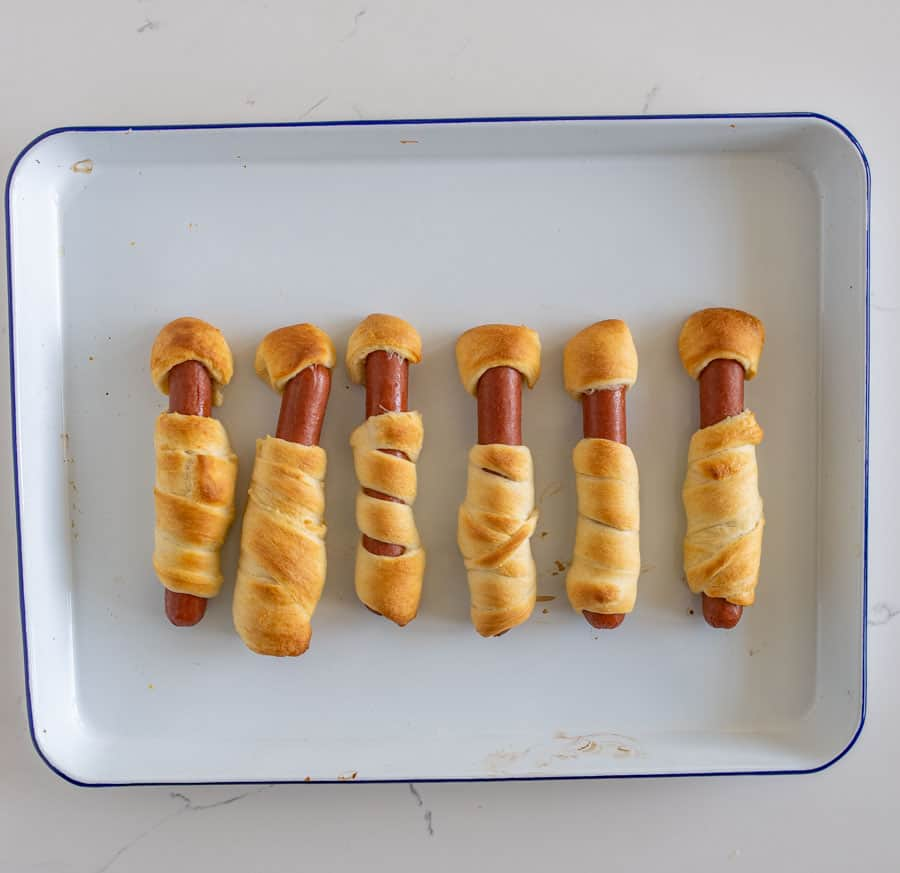Halloween mummy hot dogs are the cutest little festive snacks (reminiscent of pigs in a blanket) for a fun and creative Halloween party food! You'll be the talk of the Halloween party with these adorable mummy hot dogs, and the best part is that they only take 3 ingredients and a few minutes to make! #mummydogs #mummyhotdogs #crescentdogs #crescentrolls #pigsinablanket #halloweenrecipes #halloweensnacks