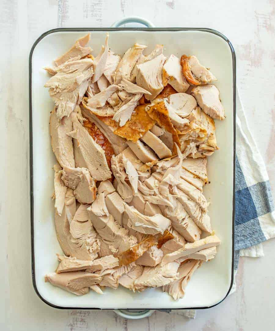 The entire turkey breast is cut up inside the white rectangle dish on top of a blue and white checkered dish towel.
