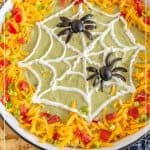 A bowl of Halloween Bean Dip with a Spider Web and Spider decoration atop guacamole, shredded cheese, diced tomatoes and scallions